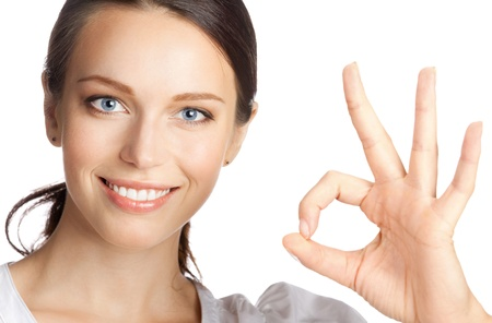 Happy smiling beautiful young business woman showing okay gesture, isolated over white background photo