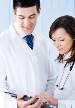 Portrait of two young medical people working together at office photo