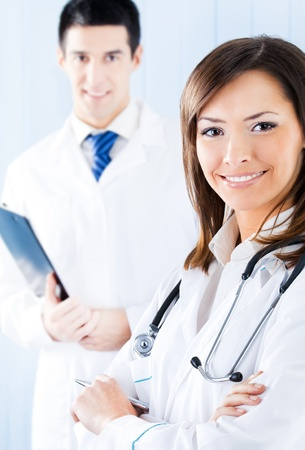 Portrait of two happy smiling young medical people at office. Focus on woman. photo