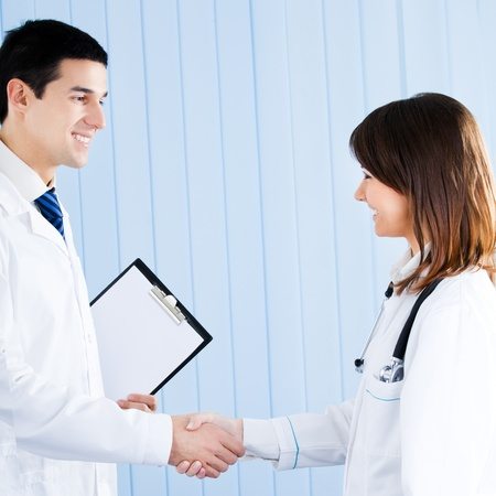 Two happy smiling young medical people handshaking at office photo