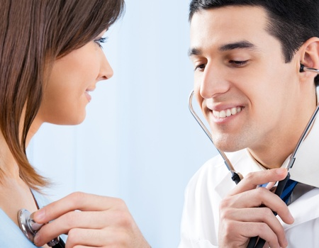 Happy smiling doctor with stethoscope and female patient at office photo