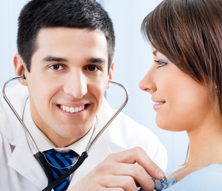 Happy smiling doctor with stethoscope and female patient at office Stock Photo - 10993735