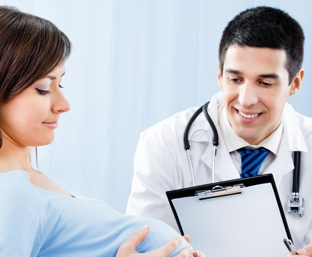 Portrait of happy smiling doctor and pregnant young woman, at office photo