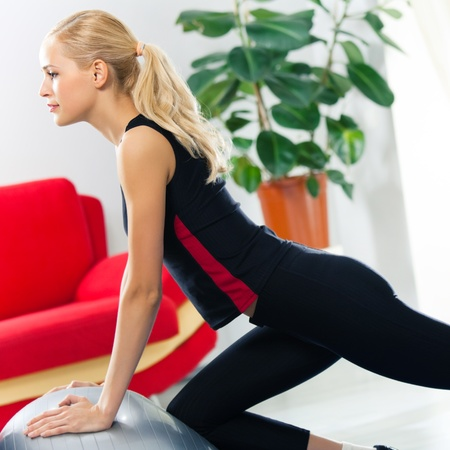 shaping: Portrait of young happy smiling woman in sportswear, doing fitness exercise with fit ball, at home Stock Photo
