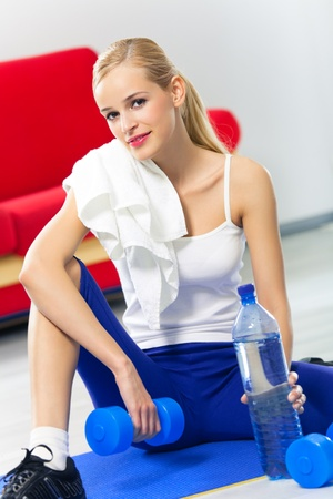 terry: Woman in sportswear with dumbbells, bottle of water and terry towel, at home Stock Photo