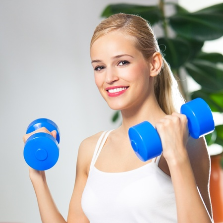 Portrait of young happy smiling woman in sportswear, doing fitness exercise with dumbbells, at home photo