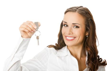 Jonge gelukkig lachende zakenvrouw of makelaar met sleutels van nieuwe huis, op een witte achtergrond