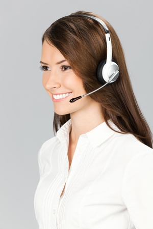 Portrait of happy smiling cheerful customer support phone operator in headset, over grey background Stock Photo - 11080308