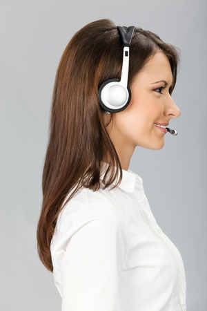 Portrait of happy smiling cheerful customer support phone operator in headset, over grey background photo