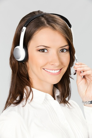 Portrait of happy smiling cheerful customer support phone operator in headset, over grey background Stock Photo - 11080314