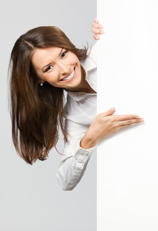 blank area: Happy smiling young business woman showing blank signboard, over grey background