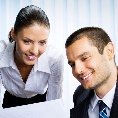 Two young happy smiling successful businesspeople working with document or contract at office photo
