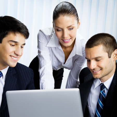 Three happy smiling successful business people working with laptop at office photo