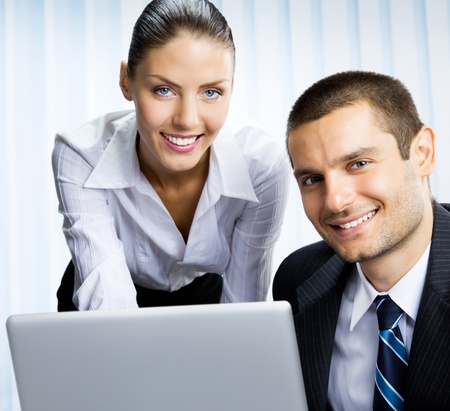 net meeting: Two happy smiling cheerful business people working with laptop at office
