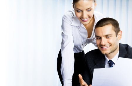 businessteam: Two young happy smiling successful businesspeople working with document or contract at office
