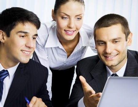 Three happy smiling successful business people working with laptop at office Фото со стока