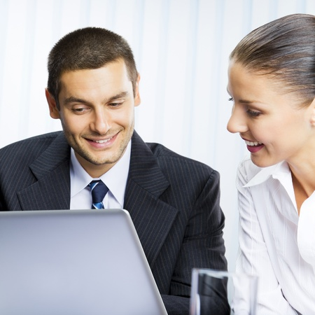 Two happy smiling cheerful business people working with laptop at office