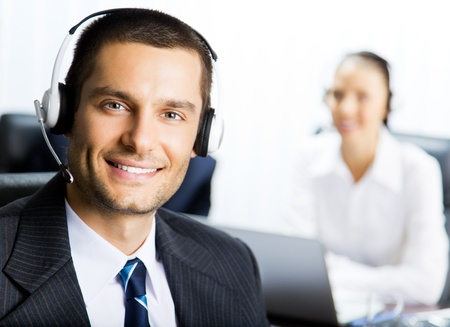 Portrait of happy smiling customer support phone operator at workplace