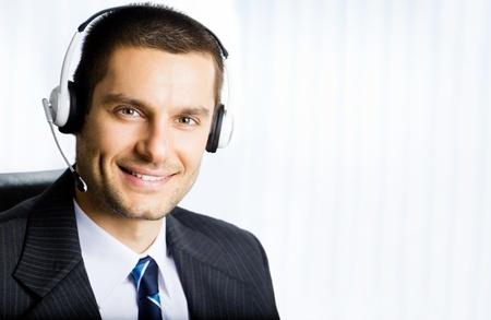 Retrato de feliz sonriendo operador telefónico al cliente apoyo en el auricular en la oficina. Puede utilizar la parte derecha de lema, texto o banner.