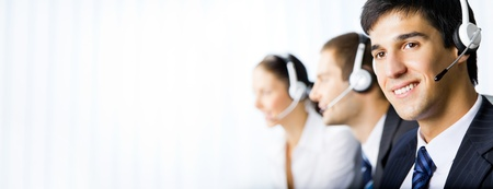 call center office: Three happy smiling young customer support phone operators at workplace. You can use left part for slogan, big text or banner. Stock Photo