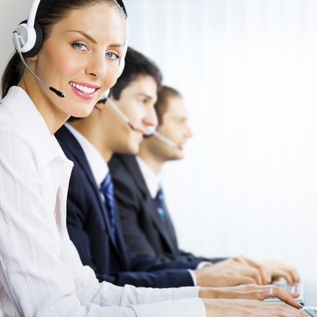 customer assistant: Three happy smiling young customer support phone operators at workplace Stock Photo