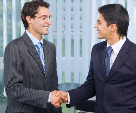 handshaking: Two happy smiling businesspeople, or business man and client, handshaking at office