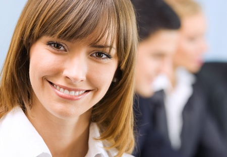 businessteam: Portrait of happy smiling young business woman and colleagues on background, at office Stock Photo