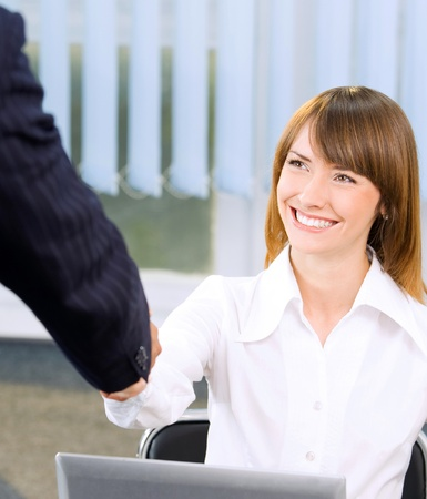 handshaking: Two happy smiling businesspeople, or business woman and client, handshaking at office
