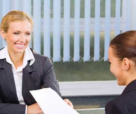 job interview: Two young happy smiling successful business women working with document or contract at office Stock Photo