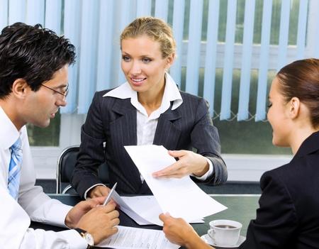 firmando: Tres sonriente feliz la gente de negocios que trabajan con el documento en la oficina