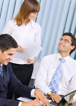 Three happy smiling business people working with document at office  photo