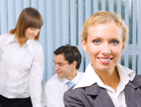 Portrait of happy smiling young business woman and colleagues on background, at office photo