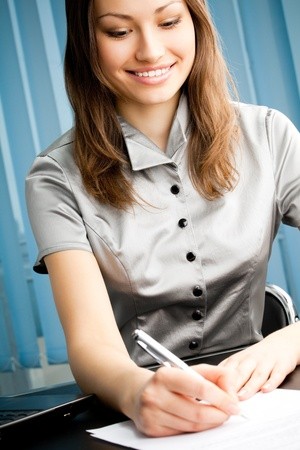 Portrait of writing happy smiling business woman working at office photo