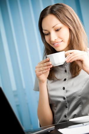 social drinking: Portrait of happy smiling business woman with coffee working with laptop at office Stock Photo
