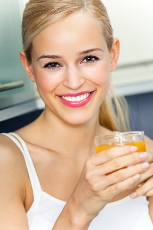 Portrait of young woman with orange juice, indoors Stock Photo - 11292226