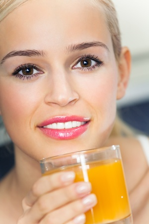 Portrait of young woman with orange juice, indoors photo