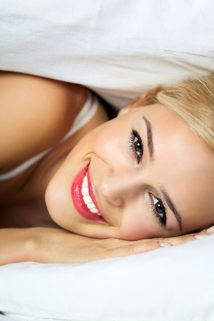 awakening: Portrait of young happy smiling woman waking up at bedroom