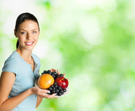 part i: Young happy smiling woman with plate of fruits, outdoor. To provide maximum quality, I have made this image, by combination of two photos. You can use right part for slogan, big text or banner.