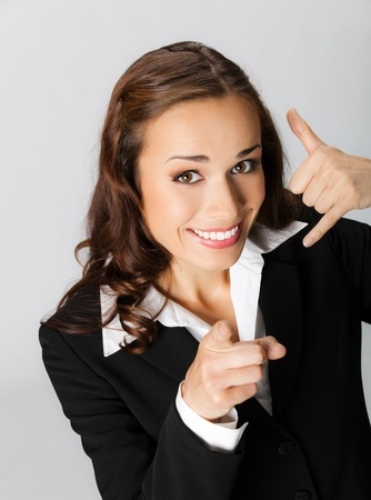 Young happy smiling business woman with call me gesture, over grey background Stock Photo - 11292266