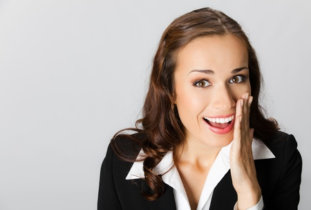 hands in mouth: Portrait of happy smiling young business woman covering with hand her mouth, over grey background Stock Photo