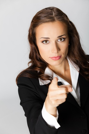Portrait of young serious business woman pointing finger at viewer, over grey background photo