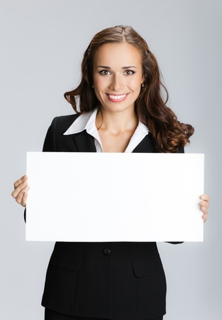 placard: Happy smiling young business woman showing blank signboard, over grey background