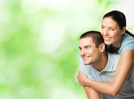 Portrait of young happy smiling attractive couple outdoors, with copyspace photo