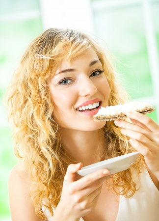 Portrait of young happy woman eating crispbread with cheese at home photo