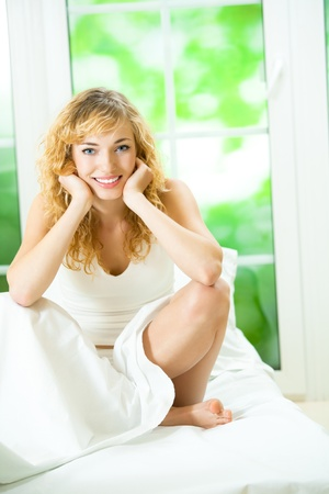 Portrait of beautiful young happy smiling woman waking up at bedroom photo