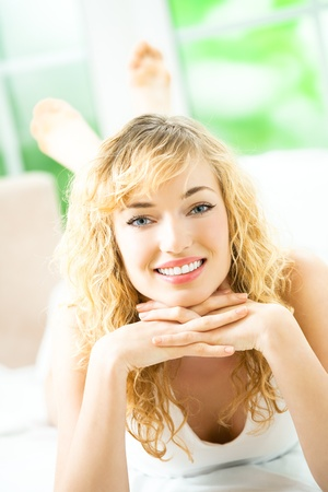 lazyness: Portrait of beautiful young happy smiling woman waking up at bedroom Stock Photo