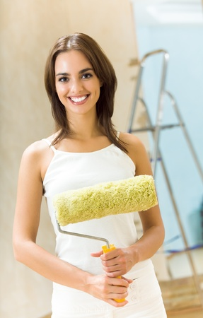 occupancy: Young happy smiling beautiful woman with paint roller in new house