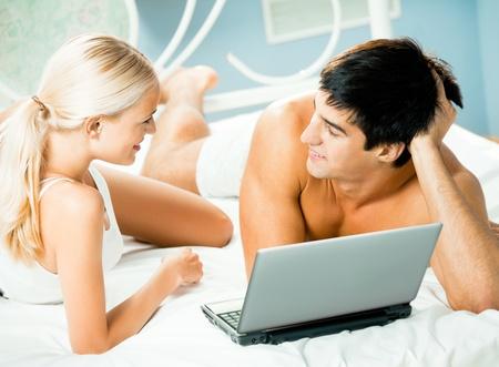 enamorados en la cama: Pareja joven sonriente feliz de trabajo con ordenador portátil en dormitorio