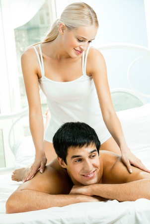 Young beautiful couple making massage in bed Stock Photo - 11872899