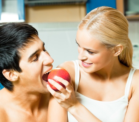 Young happy couple eating apple at home photo